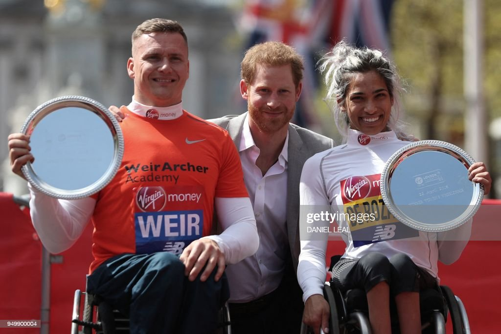 Britain's Prince Harry (C) poses with the elite men's and women's wheelchair winners Britain's David Weir (L) and Australia's Madison de Rozario at the 2018 London Marathon in central London on April 22, 2018.