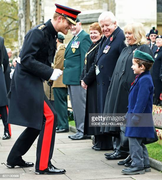 Britain's Prince Harry reacts after shaking hands with a young boy during his visit to the Field of Remembrance at Westminster Abbey in central...