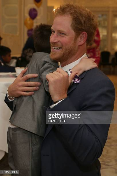 Britain's Prince Harry reacts as he greets Inspirational Child Award Winner Ollie Carroll as he attends the WellChild Awards in London on October 3...