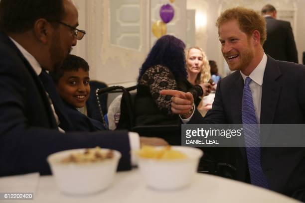 Britain's Prince Harry reacts as he meets Most Caring Child Award Winner Armaan Aslam and his father Mohammad as he attends the WellChild Awards in...