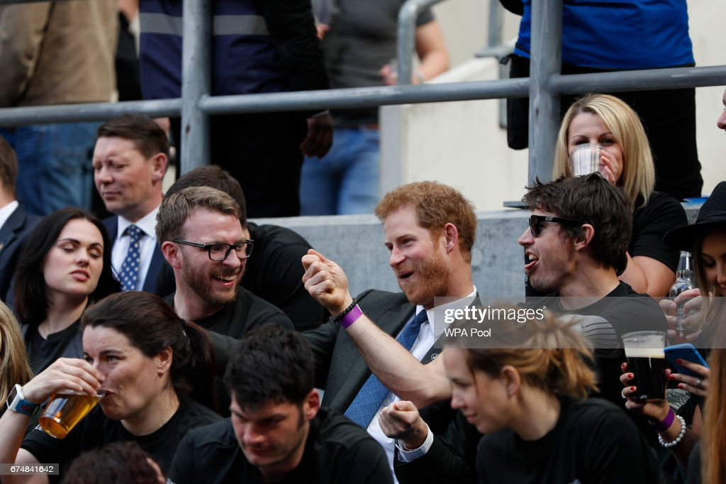 Britain's Prince Harry (C) reacts as he sits with competitors from the 2014 and 2016 Invictus Games in the crowd watching the annual Army Navy armed forces rugby match at Twickenham stadium on April 29, 2017 in London, England. Prince Harry attended the Army Navy match at Twickenham as Patron of the Invictus Games Foundation, which is the Official Charity of the day for this year's match. The Army Navy Match is the annual rugby union match between the senior XV teams of the Royal Navy and British Army. This year sees the 100th fixture.