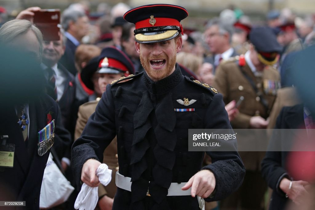 Britain's Prince Harry reacts as he talks with veterans and serving members of the armed forces during his visit to the Field of Remembrance at Westminster Abbey in central London on November 9, 2017. In the run-up to Armistice Day, many Britons wear a paper red poppy -- symbolising the poppies which grew on French and Belgian battlefields during World War I -- in their lapels. / AFP PHOTO / Daniel LEAL
