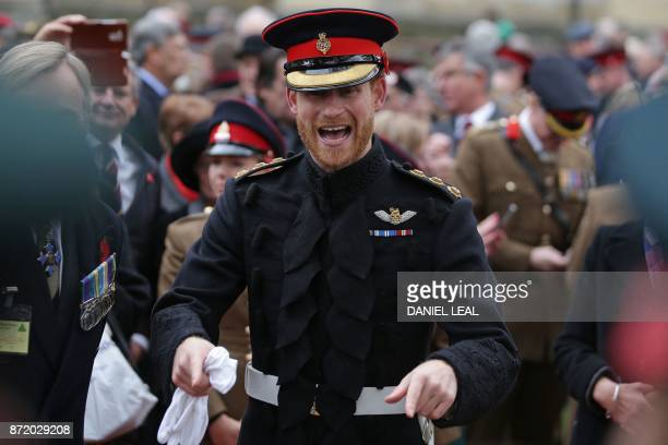 Britain's Prince Harry reacts as he talks with veterans and serving members of the armed forces during his visit to the Field of Remembrance at...