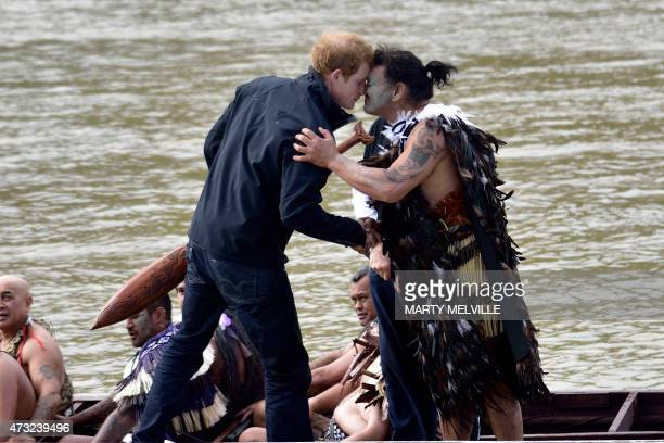 Britain's Prince Harry receives a Hongi from a Maori warrior after climbing out of a waka on the Whanganui river during a visit to Whanganui on May...