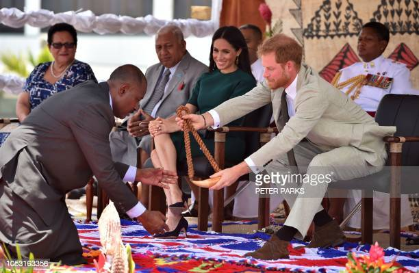 Britain's Prince Harry receives a whale tooth necklace as his wife Meghan Duchess of Sussex looks on during a farewell ceremony at Nadi airport on...
