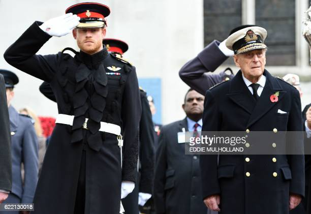 Britain's Prince Harry salutes as he stands alongside his grandfather Britain's Prince Philip Duke of Edinburgh during their visit to the Field of...