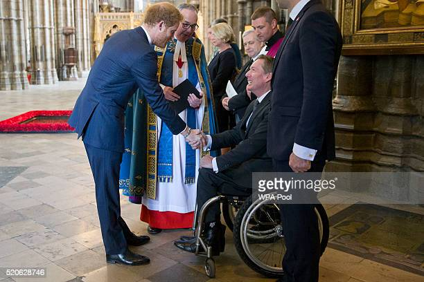Britain's Prince Harry shakes hands with British journalist Frank Gardner after a service of commemoration for victims of the 2015 terrorist attacks...