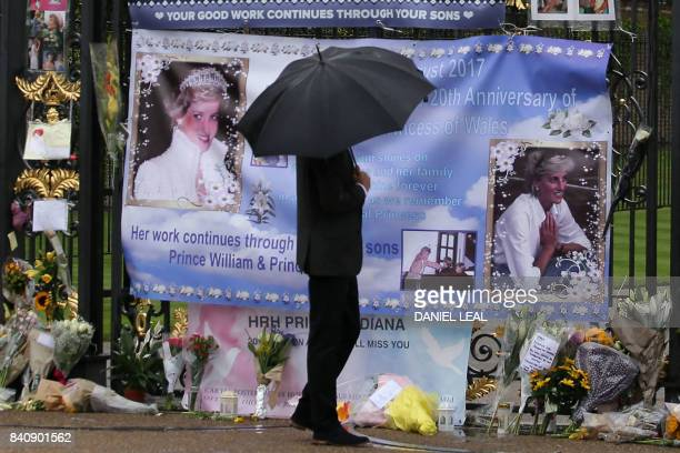Britain's Prince Harry shelters under an umbrella as he looks at tributes left by members of the public at one of the entrances of Kensington Palace...