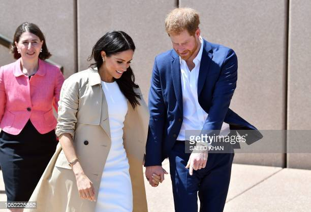 Britain's Prince Harry shows gaps on the ground to his wife Meghan as they walk outside the Sydneys iconic Opera House on October 16 2018 Prince...