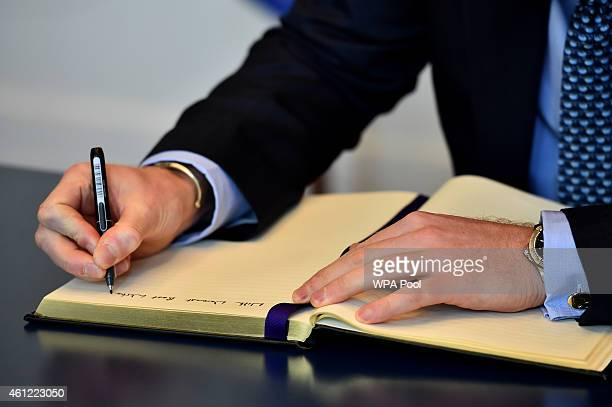 Britain's Prince Harry signs a book of condolence at the French embassy for the 12 victims of the attack on the Paris offices of satirical weekly...