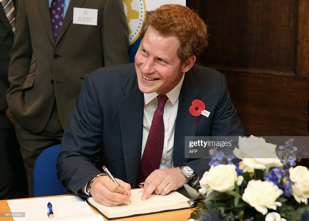 Britain's Prince Harry signs the visitors book during a visit to the Headway brain injury association as he officialy opens the Bradbury House, the charity's new headquarters, in Nottingham on April 25, 2013.