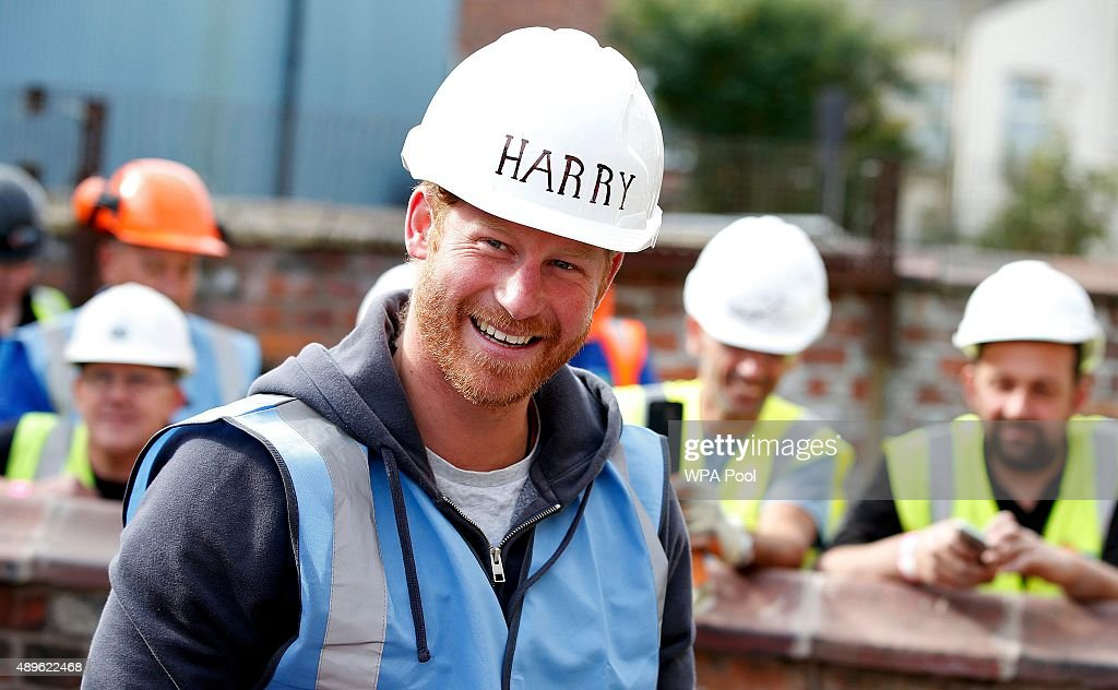 Britain's Prince Harry smiles as he prepares to lay paving slabs as he helps to renovate homes for ex-service personnel as part of the BBC television DIY SOS series on September 23, 2015 in Manchester, England. Prince William and Prince Harry visited Manchester on Wednesday where they helped to renovate homes for ex-service personnel as part of the BBC television DIY SOS series.