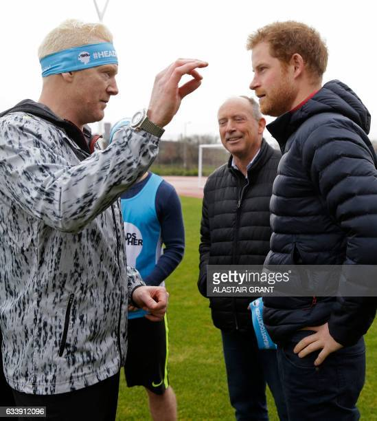 Britain's Prince Harry speaks to former British Olympic athlete Iwan Thomas as he prepares to take part in a short relay race, during a training...