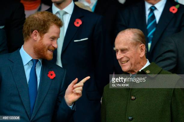 Britain's Prince Harry speaks with his grandfather Prince Philip as they watch the final match of the 2015 Rugby World Cup between New Zealand and...