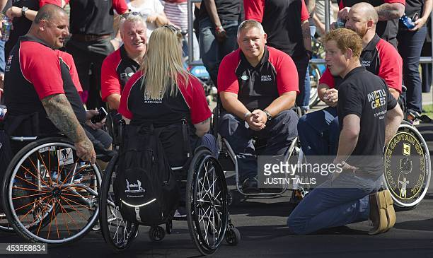 Britain's Prince Harry speaks with injured service personnel during the announcement of the British team for the Invictus Games in London on August...