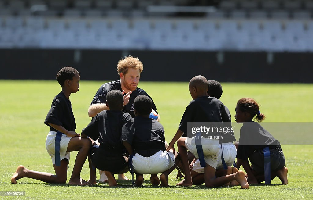 Britain's Prince Harry (3rdL) speaks with local kids prior to play a game of TAG rugby with them, on December 1, 2015 in Durban, as part of his four-day South Africa trip. / AFP / ANESH
