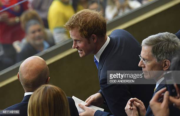Britain's Prince Harry speaks with officials as he arrives to attend the Group D football match between Costa Rica and England at The Mineirao...