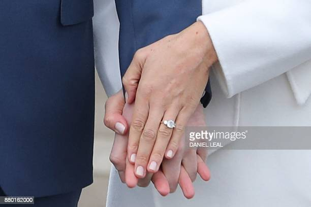 TOPSHOT Britain's Prince Harry stands with his fiancée US actress Meghan Markle as she shows off her engagement ring whilst they pose for a...