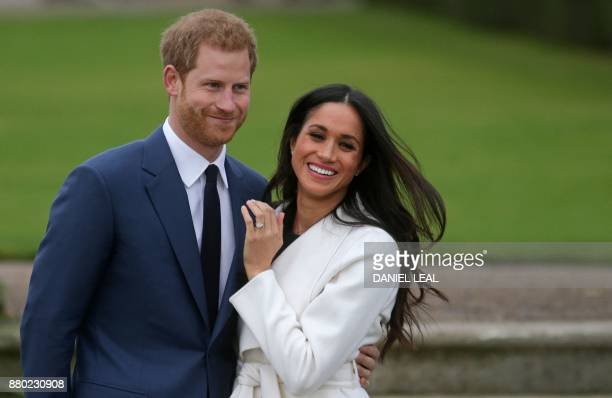 Britain's Prince Harry stands with his fiancée US actress Meghan Markle as she shows off her engagement ring whilst they pose for a photograph in the...