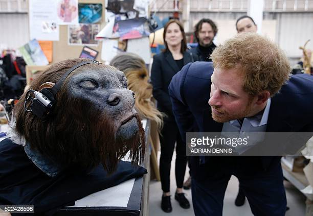 Britain's Prince Harry takes a closer look at a robotic mask during a tour of the Star Wars sets at Pinewood studios in Iver Heath west of London on...