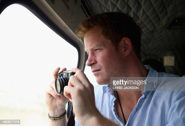 Britain's Prince Harry takes a photograph out of the window of a Lesotho Army Helicopter as he travels over the Muluti Mountains on the way to a herd...