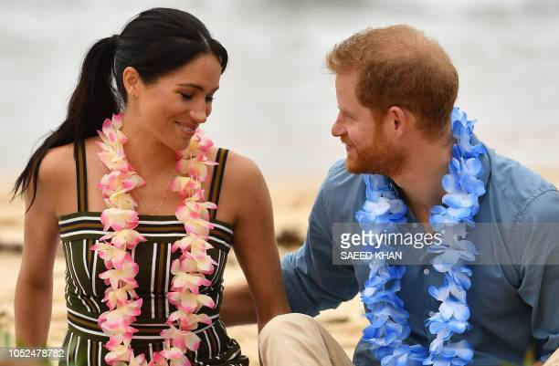 Britain's Prince Harry takes care of Meghan Duchess of Sussex as they attend a Fluro Friday session run by OneWave a local surfing community group...