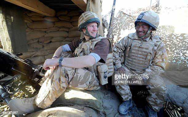 Britain's Prince Harry talks to a Gurkha January 02 after firing a 50mm machine gun at Taliban fighters from the observation post at JTAC Hill close...