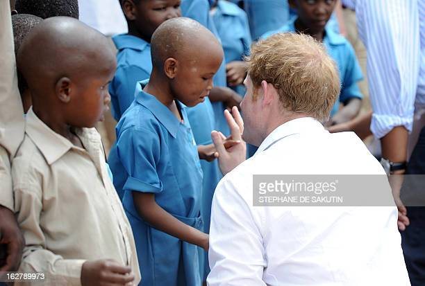 Britain's Prince Harry talks to a pupil at a primary school for blind children on February 27, 2013 in Maseru. The prince visited his charity...
