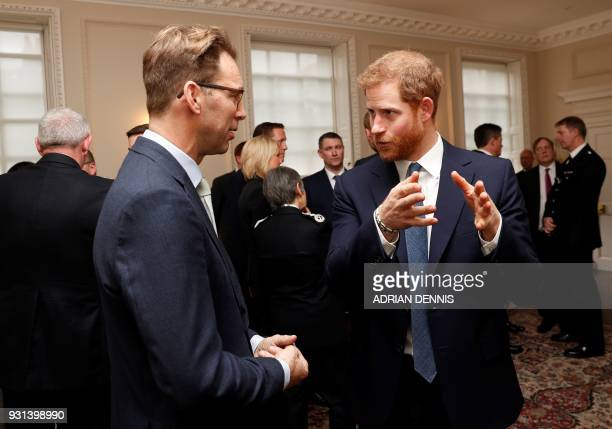 Britain's Prince Harry talks with MP Tobias Ellwood who recieved a police bravery award in recognition for his actions in trying to help save the...