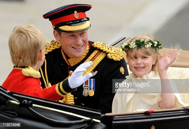 Britain's Prince Harry travels with a bridesmaid and a page boy in an Ascot Landau carriage along the Processional Route to Buckingham Palace in...