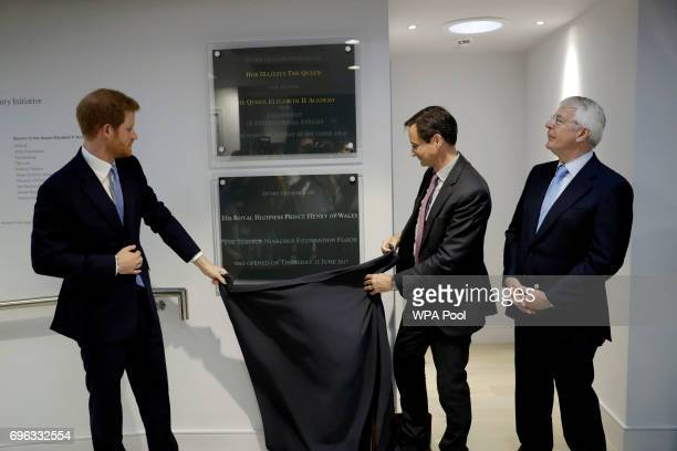 Britain's Prince Harry unveils a plaque with Chatham House director Robin Niblett, centre, watched by the Chair of their Panel of Senior Advisers,...