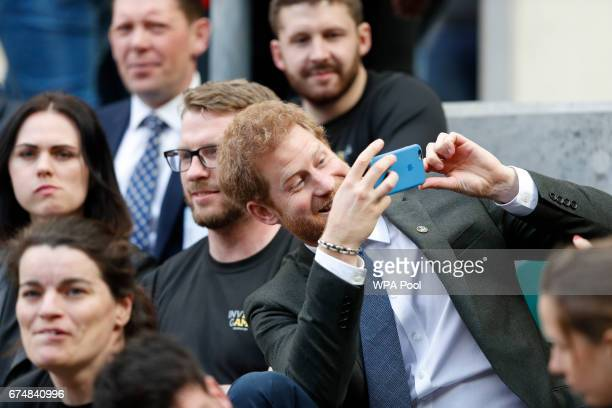 Britain's Prince Harry uses a smartphone to take a photograph as he sits with competitors from the 2014 and 2016 Invictus Games in the crowd watching...