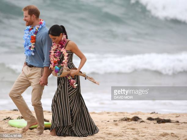 TOPSHOT Britain's Prince Harry walks with his wife Meghan Duchess of Sussex as they meet the local community at Bondi Beach in Sydney on October 19...