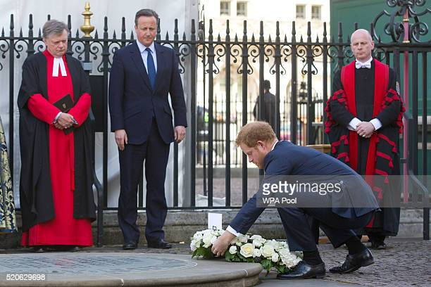 Britain's Prince Harry watched by British Prime Minister David Cameron lays a wreath at the Innocent Victims Memorial prior to a service of...