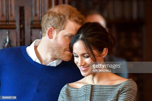 Britain's Prince Harry whispers to his fiancée US actress Meghan Markle as they watch a performance by a Welsh choir during a visit at Cardiff Castle...