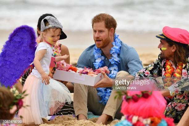 Britain's Prince Harry with his wife Meghan Duchess of Sussex receives a box of tropical garlands from a child as they attend a Fluro Friday session...