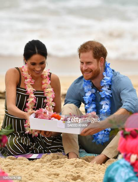 Britain's Prince Harry with his wife Meghan Duchess of Sussex receives a box of tropical garlands as they attend a Fluro Friday session run by...