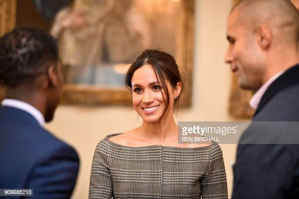 Britain's Prince Harry's fiancée US actress Meghan Markle chats with people inside the Drawing Room during a visit at Cardiff Castle in Cardiff south...