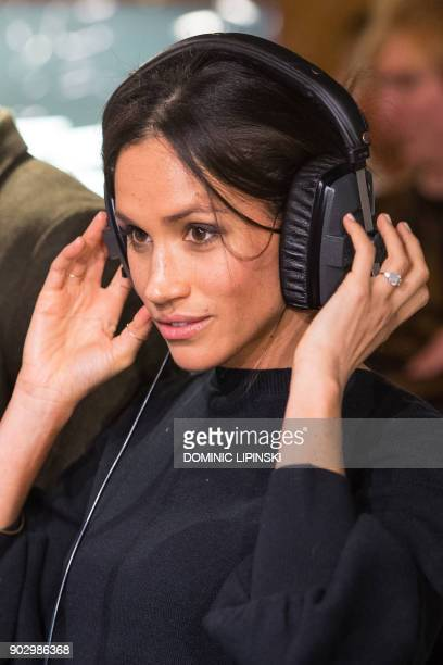 Britain's Prince Harry's fiancée US actress Meghan Markle listens to a broadcast through headphones during a visit to Reprezent 1073FM community...