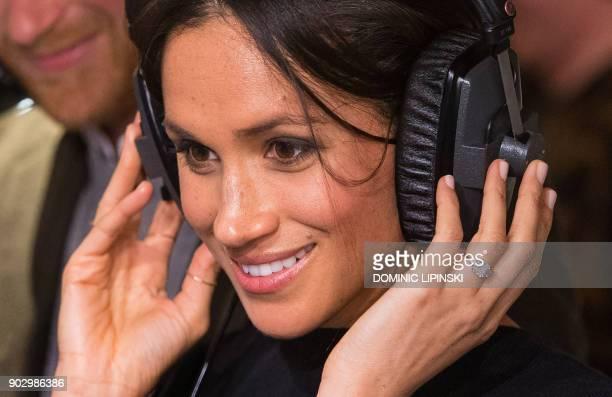 Britain's Prince Harry's fiancée US actress Meghan Markle listens to a broadcast through headphones during a visit to Reprezent 107.3FM community...