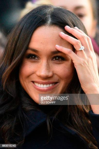 Britain's Prince Harry's fiancee US actress Meghan Markle displays her engagement ring as she greets wellwishers on a walkabout as they arrive for an...