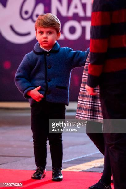 Britain's Prince Louis of Cambridge holds his mother's hand as they attend a special pantomime performance of The National Lotterys Pantoland at...