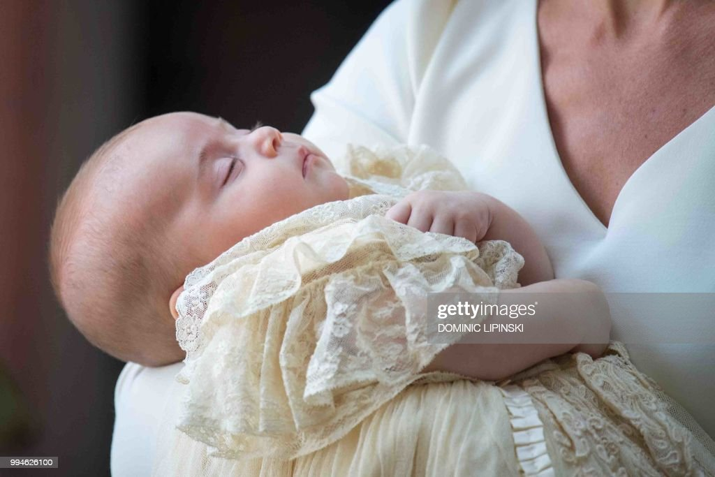 TOPSHOT - Britain's Prince Louis of Cambridge is carried by Britain's Catherine, Duchess of Cambridge on their arrival for his christening service at the Chapel Royal, St James's Palace, London on July 9, 2018.