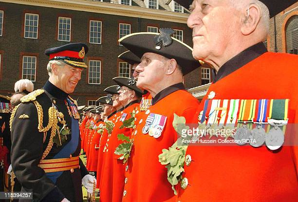 Britain's Prince of Wales inspects a group of Chelsea Pensioners at the annual Founder's Day Parade which he attended with the Duchess of Cornwall at...
