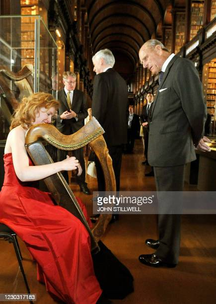 Britain's Prince Philip , Duke of Edinbourgh, listens to harpist Siobhan Armstrong play a traditional Irish harp during a tour at Trinity College in...