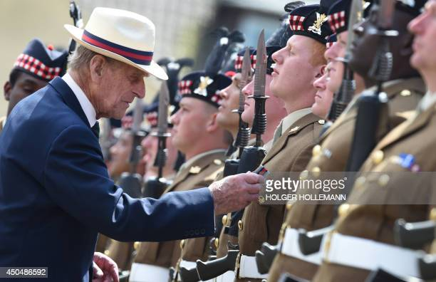 Britain's Prince Philip Duke of Edinburgh decorates a soldier of the 4th Battalion The Royal Regiment of Scotland for his service in Afghanistan at...