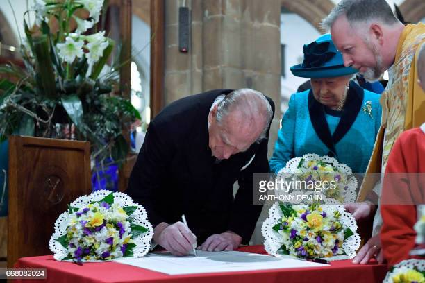 Britain's Prince Philip Duke of Edinburgh signs the guest book as Queen Elizabeth II looks on during the Royal Maundy service at Leicester Cathedral...