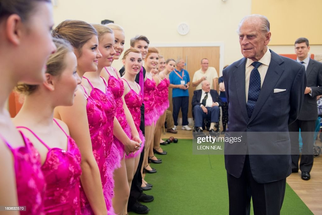 Britain's Prince Philip (R) meets pupils of the Broadland School of Dance in the ACT centre of the St Michael's Care Complex in Aylsham, eastern England, during an official visit on October 8, 2013.