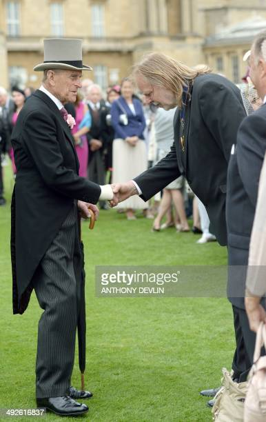 Britain's Prince Philip the Duke of Edinburgh shakes hands with British musician Rick Wakeman during the first garden party of the year at Buckingham...
