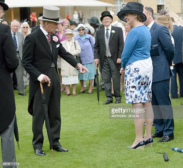 Britain's Prince Philip the Duke of Edinburgh speaks with guests during the first garden party of the year at Buckingham Palace in London on May 21...